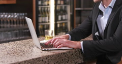 Smiling businessman typing on his laptop while drinking Stock Footage