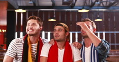 Disappointed handsome friends watching sports Stock Footage