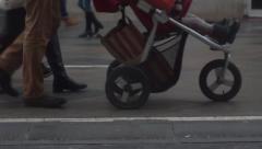 Slow motion video of unrecognizable people with baby carriage in the street - stock footage