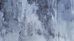 waterfall running down frozen icicles in slow motion - stock footage