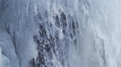 Waterfall running down frozen icicles super slow motion Stock Footage