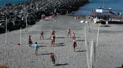 People play volleyball at the sandy bach of Playa Torviscas. Tenerife Stock Footage