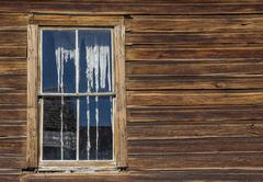 Window and ripped curtains of a house in Bodie - stock photo