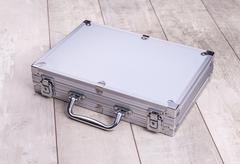 Metallic suitcase on wood background Stock Photos