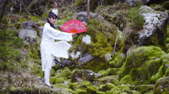 Exercising pose in traditional white kimono and red Chinese fan 4K Stock Footage