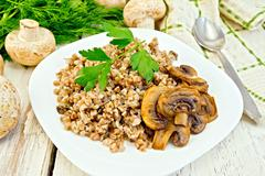Buckwheat with champignons in plate on light board Stock Photos
