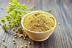 Coriander powder in bowl on board - stock photo