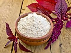 Flour amaranth in clay bowl on board with flower Stock Photos