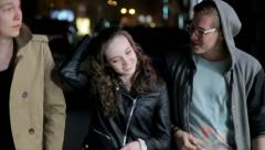 Two guys and a girl walking through the city at night. happy - stock footage