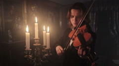 girl playing the violin next to the candles. Baroque style - stock footage