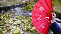 Chinese fan in hand opened in front of river source 4K Stock Footage