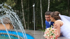 Happy bride and groom standing near the fountain in the park Stock Footage