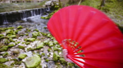 Opening and closing red Chinese fan in front of natural water source 4K Stock Footage