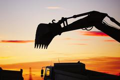 Silhouette of the backhoe in the building site Stock Photos