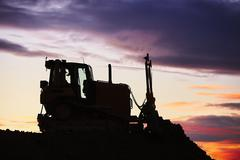 Silhouette of the bulldozer in the building site - stock photo