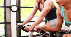 Fit people working out on exercise bike Stock Footage