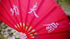 Playing with red Chinese fan with characters in front of river stream 4K Stock Footage