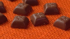 Chocolate candies over orange background - stock footage