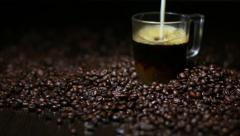 Pouring milk into cup of coffee on dark background Stock Footage