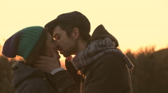 Couple of young lovers kissing, romantic sunset Stock Footage