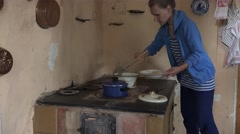 Woman take food from pot with spoon in kitchen clay stove. 4K Stock Footage