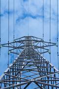 Power pole with high voltage against the blue sky Stock Photos