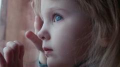 Little cute girl behind window in winter Stock Footage