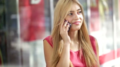 Attractive young blonde lady using smart phone in a city mall Stock Footage