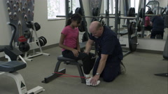 Therapist working with teenage girl with elastic band leg exercise. Stock Footage