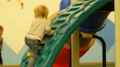 Little kid girl playing climbing a playgroung slide Stock Footage