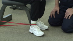 Tight shot of Therapist working with teenage girl with elastic band leg Stock Footage