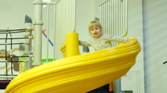 Kid child girl slides down on the pope in a playground - stock footage