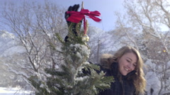 Group Of Teens Decorate A Snow Covered Christmas Tree Outside Stock Footage