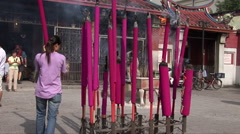 Malaysian woman positions large incense stick - stock footage