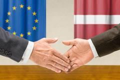 Representatives of the EU and Latvia shake hands - stock photo