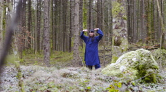 Person in blue kimono make Kung Fu forms in middle of forest 4K Stock Footage