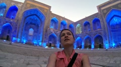 Delighted girl tourist in the courtyard of the Sher-Dor Madrasah Stock Footage