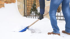 Man digging snow with shovel near house Stock Footage