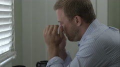 Tight shot of stressed man at desk taking some pills. - stock footage