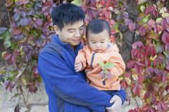Happy Chinese father and son in front of Boston Ivy - stock photo