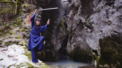 Kung Fu pose with katana sword over head beside rock canyon 4K Stock Footage