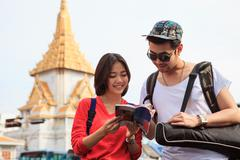 couples of asian younger traveling man and woman reading message in traveler - stock photo