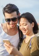 close up face of younger asian man and woman looking to smart phone use for y - stock photo
