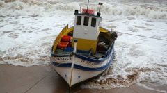 Fishing boat on beach shore coast, strong storm waves, Portugal Stock Footage