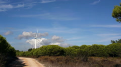 Windmill electricity generator spins in wind, bright blue sunny day, long shot Stock Footage