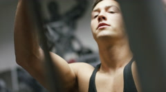 Muscular young man using a weights machine in the gym, in slow motion Stock Footage