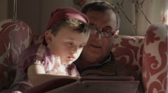 A grandparent is reading a story book to his granddaughter and grandson. The - stock footage