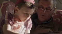 A grandparent is reading a story book to his granddaughter and grandson. The Arkistovideo