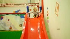 Kid child girl slides down on the pope in a playground slow motion - stock footage