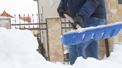 Man with snow shovel cleans sidewalks in winter. Stock Footage